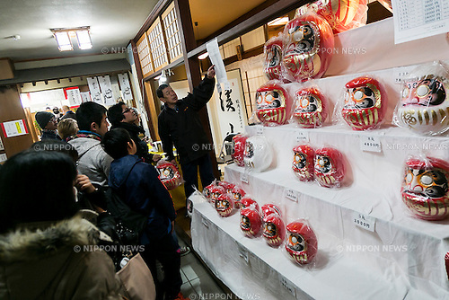 A merchant sales Daruma dolls at the Shorinzan Daruma Temple in Takasaki City, Gunma Prefecture on January 6, 2016, Japan. Every year thousands of people visit the country's most famous Daruma market (Daruma ichi) held at the Shorinzan Daruma Temple on January 6 and 7. Takasaki City, is known as the capital of Daruma dolls and about 80% of Japan's Daruma are produced there. According to the tradition, Daruma dolls are sold without pupils painted on their eyes. People color in one pupil when a wish is made or a goal set, and when the wish comes true or the goal is achieved they fill in the other pupil. At the end of the year, used Daruma dolls are returned to the temple to be burned. (Photo by Rodrigo Reyes Marin/AFLO)