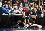 UNCASSVILLE, CT-031918JS06- WATR's Dave Grant, left, grabs is arm after being injured while he and fellow WATR personnel Allie Vestro, center, and Bob Sagendorf, right, react as Sacred Heart's Andre Anderson and Noah Francisco collide with with their table during the Division 1 championship game against Notre-Dame-Fairfield Sunday at the Mohegan Sun Area. <br />  Jim Shannon Republican-American
