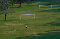 Young girl kicks the soccer ball to a coach before the start of practice on the soccer fields below Hoover Reservoir