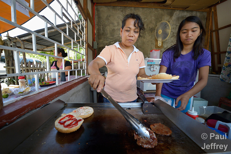 Maria Theresa Malalo is a survivor of human trafficking in Germany, where she worked as a domestic worker in the house of an Israeli diplomat. Now back home in Batangas, in the Philippines, she earns a living preparing and selling food, like siomai--Chinese dumplings that are very popular in the Philippines. Here she prepares hamburgers on a grill with assistance from a friend of one of her three daughters.  Malalo, who is pursuing a case against her former employer in Germany for unpaid back salary, has been assisted by the Batis Center for Women, which helped her establish her small restaurant.