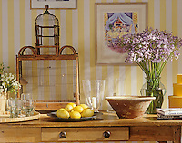 Items are displayed on a wooden sideboard. A wooden bird cage, a flower arrangement of pale purple flowers, glassware and a plate of lemons amongst them.