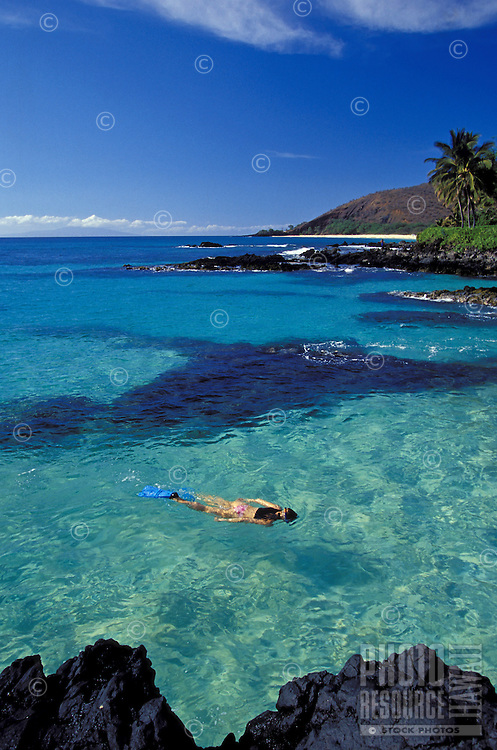 Girl snorkels in clear water at Makena, Maui.