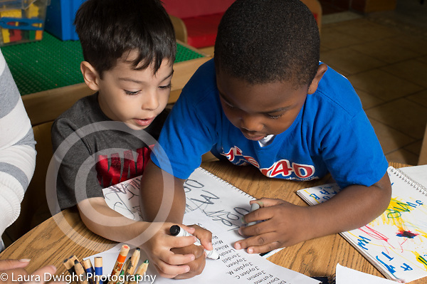Preschool 3-4 year olds two boys working together one boy helping guide the other boy's hand as he writes on sign in sheet