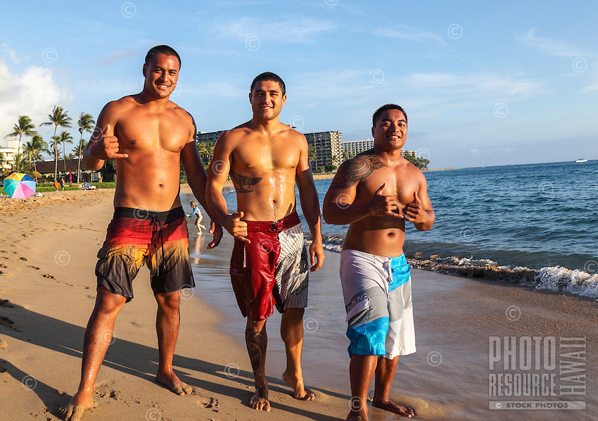 Maui locals offer the shaka sign at Ka'anapali Beach at sunset; condominiums and other accommodations are in the distance. (NOTE: The three men in the foreground are model released; the others in the distance are not.)