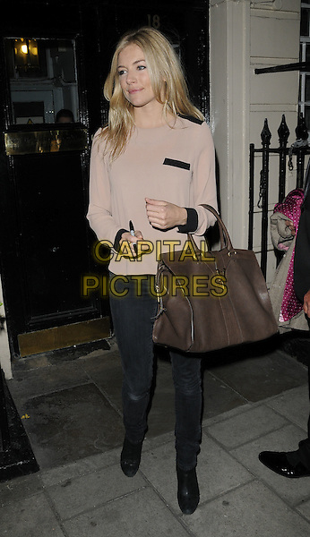 """SIENNA MILLER .Seen leaving after the evening performance of """"Flare Path"""", Theatre Royal Haymarket, London, England, UK, 26th April 2011..full length brown bag grey gray jeans beige top jumper pen .CAP/CAN.©Can Nguyen/Capital Pictures."""
