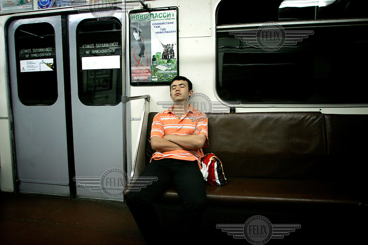 A man sleeps while riding on a metro in the capital.