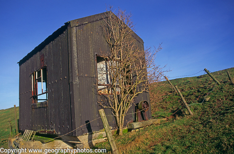A082NF Old abandoned corrugated pump house on sea wall dyke East Anglia England Butley Suffolk