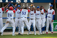 27 September 2009: First base Ariel Borrero of Cuba is congratulated by teammates as he hits a two run home run off pitcher Brad Lincoln to tie the score during the 2009 Baseball World Cup gold medal game won 10-5 by Team USA over Cuba, in Nettuno, Italy.
