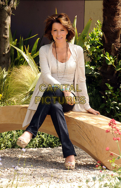 NATASHA KAPLINSKY .Chelsea Flower Show Press and VIP Day, London, England, UK, .May 23rd, 2011..full length black trousers beige nude cardigan shoes sitting garden bench .CAP/WIZ.© Wizard/Capital Pictures.