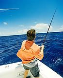 USA, Florida, man reeling in a fish at sea, rear view, Islamorada