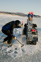 Sunday March 11, 2007   ----    Trail Breaker Steve Graham chops a hole in the ice to put a trail stake as the trail breakers leave the slough at Unalakleet on Sunday morning.