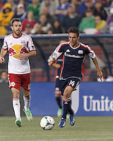 New England Revolution midfielder Diego Fagundez (14) on the attack. In a Major League Soccer (MLS) match, the New England Revolution (blue) tied New York Red Bulls (white), 1-1, at Gillette Stadium on May 11, 2013.