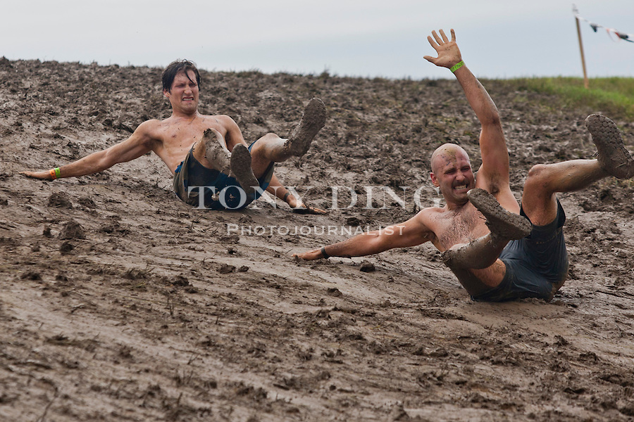 16 April 2010: Competitors slide down a muddy hill in the Tough Mudder adventure endurance race at Michigan International Speedway in Brooklyn, Michigan.