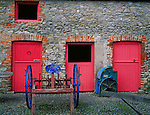 County Clare, Ireland<br /> Stone walls and cobbled stable yard with brighlty painted stable doors and horse plow at Bunratty House, Bunratty Folk Park