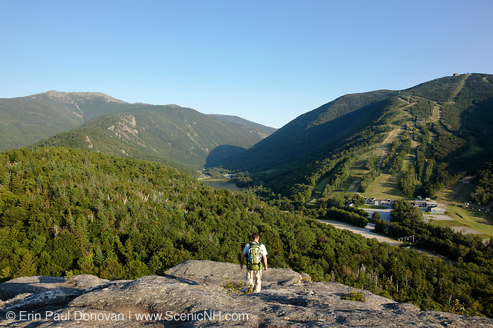 A hiker on the summit of Bald Mountain in the New Hampshire White Mountains. Franconia Notch is in the background.