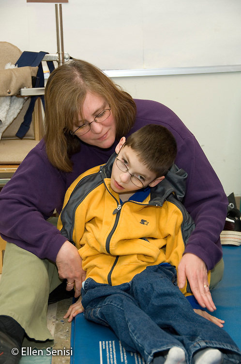 MR / Albany, NY.Langan School at Center for Disability Services .Ungraded private school which serves individuals with multiple disabilities.Physical therapist assistant manipulates child's limbs to stretch and move body. Boy: 9, cerebral palsy, limited verbal output with expressive and receptive language delays.MR: Rub1; Tho15.© Ellen B. Senisi