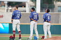 Frisco RoughRiders third baseman Charles Leblanc (12), pitcher Esmerling Vasquez (35) and second baseman Andretty Cordeo (4) during the national anthem before a Texas League game against the Springfield Cardinals on May 6, 2019 at Dr Pepper Ballpark in Frisco, Texas.  (Mike Augustin/Four Seam Images)