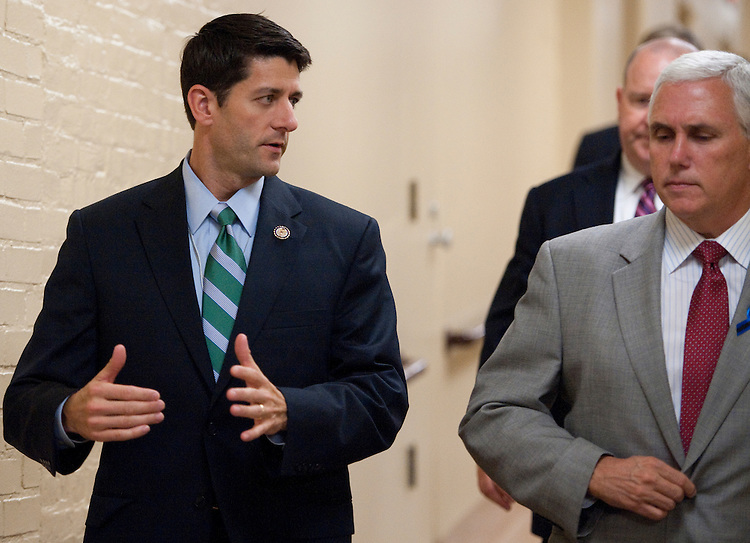 UNITED STATES - JULY 25: House Budget chairman Paul Ryan, R-Wisc., speaks with Rep. Mike Pence, R-Ind., as they arrive for a meeting of the House Republican Conference in the basement of the U.S. Capitol on Monday, July 25, 2011. (Photo By Bill Clark/Roll Call)