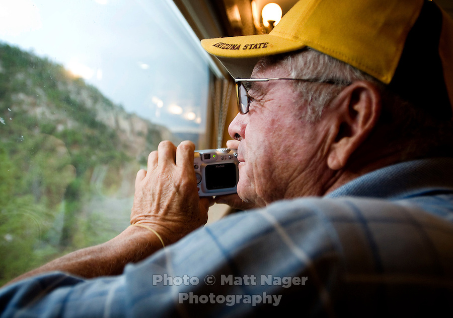 A tourist takes a photo outside the moving train through Copper Canyon near Creel, Mexico. Three canyons crisscross and meet at this point lending to the most dramatic cliffs and drops in the canyon...PHOTOS/ MATT NAGER