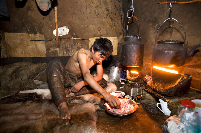 Vitya Nutetgevev, a young Chukchi reindeer herder, eating a morning meal of raw frozen reindeer meat inside the Polog of a Yaranga. Chukotskiy Peninsula, Chukotka, Siberia, Russia