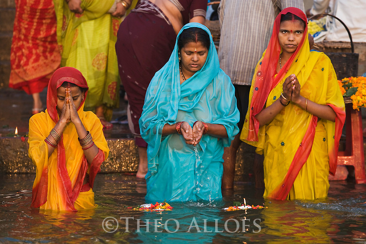 Indian women praying and giving offerings in Ganges River;  Varanasi has been a cultural and religious center in northern India for several thousand years, Varanasi, Uttar Pradesh, India