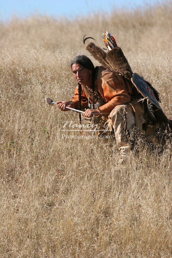 A Native American Indian man crouching in the dead grasses hunting game or going into battle