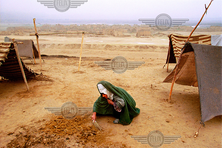 © Tim Dirven / Panos Pictures..Mazar-e-Sharif, Afghanistan. December 2001...Shirin Tagab refugee camp. A woman is scraping together sheep droppings in front of her tent, which she will use for heating and cooking fuel once they are dried.