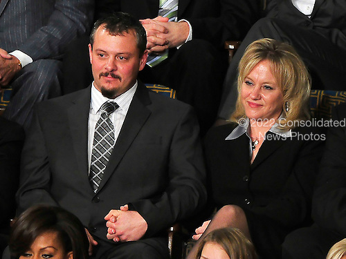 Brandon Fisher, left, holds the hand of his wife, Julie, right as United States President Barack Obama mentions their company in his State of the Union Address to a Joint Session of Congress in the U.S. Capitol in Washington, D.C. on Tuesday, January 25, 2011.  The Fishers operate Center Rock, a Berlin, Pennsylvania based company whose drilling expertise was instrumental in the rescue of the 33 miners trapped in a mine in Chile last year..Credit: Ron Sachs / CNP.(RESTRICTION: NO New York or New Jersey Newspapers or newspapers within a 75 mile radius of New York City)