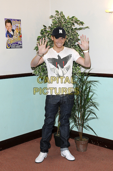 """JOE SWASH.At a press conference for the pantomime """"Cinderella"""" at Central Theatre, Chatham, Kent..December 10th, 2008.panto length full length jeans denim   white t-shirt baseball cap hat black  hands palms waving .CAP/FIN.©Steve Finn/Capital Pictures."""