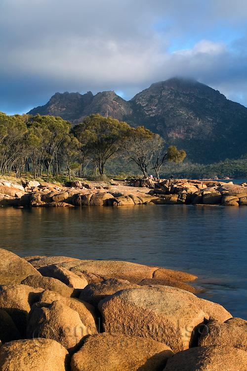 The shoreline of Coles Bay with The Hazards mountain range beyond.  Freycinet National Park, Tasmania, AUSTRALIA