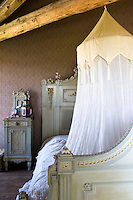 A painted bed and matching bedside cabinet is draped with an old-fashioned mosquito net