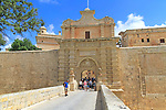 Tourists walking over moat bridge through entrance gateway of medieval city of Mdina, Malta