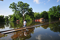 """8/13/11} Vicksburg} -- Vicksburg, MS, U.S.A. --Robert Shiers aka Peanut paddles past his hand built cabin in the woods too check on the flood waters Friday May 13,2011 Peanuts flooded cabin on Chickasaw Road was a cabin in the woods is now a cabin on the flooded Mississippi River.  Hope and faith float as the Mississippi River continues to rise around the Kings Community on Friday the 13th of May 2011. """"Peanut """" aka Robert Shiers navigates his """"John Boat"""" down Chickasaw Rd. in Vicksburg Mississippi. His hand built ,self designed cabin which sits on 14ft. stilts on the old Belle Meade Plantation was on a 5acre wheat field that is now inundated with water and only able to get to by boat.  No mail today for residents of the Kings Community in Vicksburg MS Friday May 13, 2011.The Mississippi River in Vicksburg, Mississippi is expected to crest at a record 58.5 feet. The water is moving at 2.2million cubic feet per second, to put it in perspective it would fill the SuperDome in New Orleans in 30 seconds. Pictured is the historic Yazoo Valley Railroad Station in downtown Vicksburg. The River is flooding over 1.2 million acres of farm land and damaging thousands of homes and disrupting thousands of peoples lives. Vicksburg a riverfront town steeped in war and sacrifice, gets set to battle an age-old companion: the Mississippi River. The city that fell to Ulysses S. Grant and the Union Army after a painful siege in 1863 is marshaling a modern flood-control arsenal to keep the swollen Mississippi from overwhelming its defenses. PHOTO©SUZI ALTMAN.COM.Photo by Suzi Altman."""
