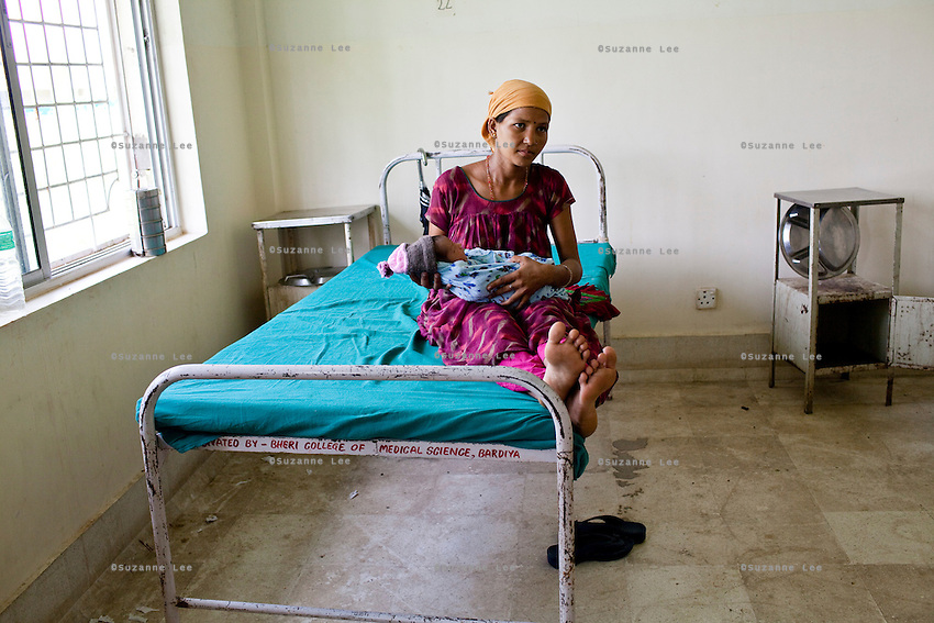 Laxmi Oli, 23, cradles her 3-day-old 2nd child, in the Bardia District Hospital one hour's walk from her village in Bardia, Western Nepal, on 29th June 2012. Laxmi had her first child at 18. In Bardia, StC works with the district health office to build the capacity of female community health workers who are on the frontline of health service provision like ante-natal and post-natal care, and working together against child marriage and teenage pregnancy especially in rural areas. Photo by Suzanne Lee for Save The Children UK