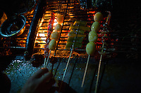 Skewers of potatos cook on a barbecue at a nameless shaokao restaurant on the sidewalk near the west gate of the Ciqikou area of Shapingba district in Chongqing, China. Ciqikou's ancient town is a major tourist destination in Chongqing, but at night, the tourists disappear and locals come out to eat from street food vendors in the area.<br /> <br /> The restaurant is run by Liu Pang Wa, whose wife and two children also help. Most of the customers there are neighborhood locals, and the restaurant stays open until 3 or 4 am. Liu Pang Wa said his specialties are eggplant, pig brain, and fish. The area is close to western banks of the Jialing River in northwestern Chongqing city.