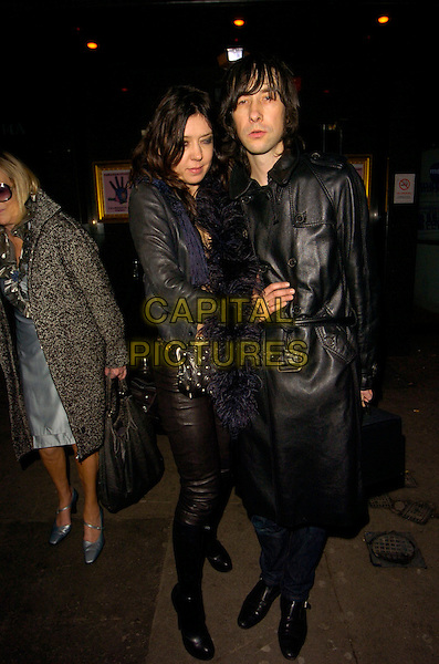 BOBBY GILLESPIE & GUEST.Kate Moss' 34th birthday party, Punk bar & club, London, England..January 16th, 2008.full length black leather jacket coat boa blue purple scarf studs studded bag purse .CAP/CAN.©Can Nguyen/Capital Pictures