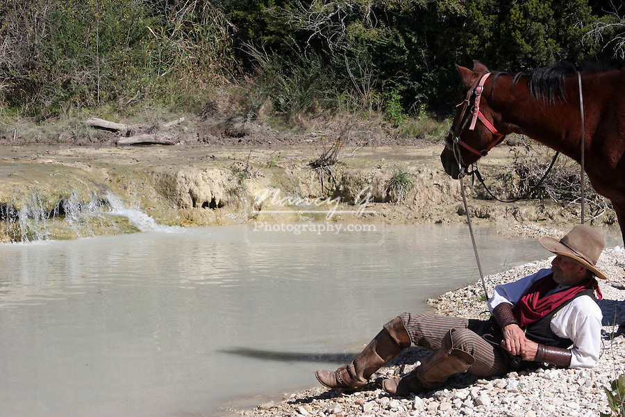 a cowboy resting by the edge of the stream