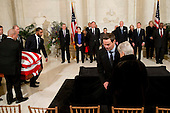 As his widow Maureen Scalia is helped to her place at front, the casket of late Supreme Court Justice Antonin Scalia is carried into the Great Hall of the United States Supreme Court for a private ceremony in Washington, DC on Friday, February 19, 2016. From back left are Counselor to the Chief Justice Jeffrey Minear, and Supreme Court Justices Elena Kagan, Samuel Anthony Alito, Jr., Ruth Bader Ginsburg, Anthony M. Kennedy, Chief Justice John G. Roberts, Jr., and Clarence Thomas. <br /> Credit: Jacquelyn Martin / Pool via CNP