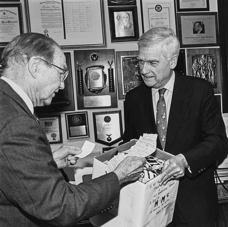 Sen. Mark Hatfield, R-Ore., handing over to Sen. Strom Thurmond, R-S.C., 7lbs of M & M, ransom for Mr. M & M being held hostage. Thurmond reading the cryptic ransom note (in his left hand).  The union station locker code where Mr. M & M is to be found by reporter E. D. Thurney, then returned to the rightful owner. Mar. 11, 1992. (Photo by Maureen Keating/CQ Roll Call)