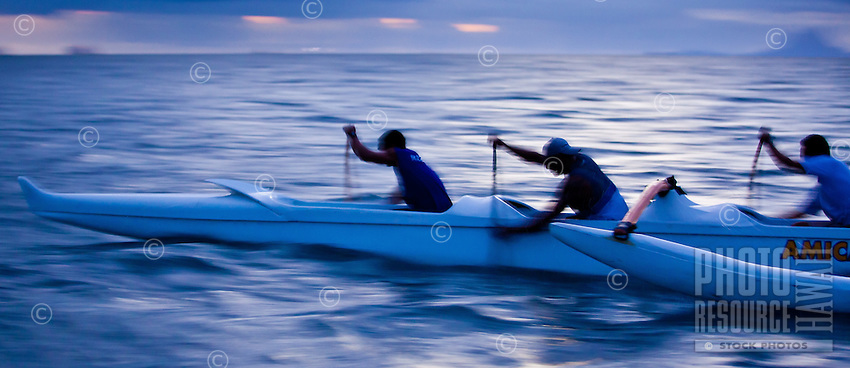 Young Tahitian men paddling six man canoe at dusk in lagoon while training for a race