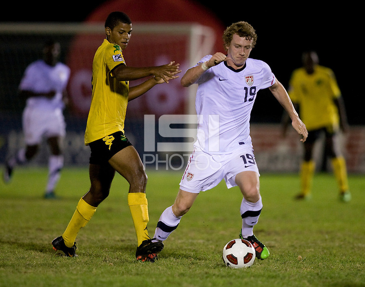 Jack McBean (19) of the United States sprints past Omar Holness (9) of Jamaica during the semifinals of the CONCACAF Men's Under 17 Championship at Catherine Hall Stadium in Montego Bay, Jamaica. The United States defeated Jamaica, 2-0.