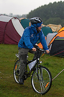 Thomas Frostberg on a bike in the rain. Photo: Magnus Fröderberg/Scouterna