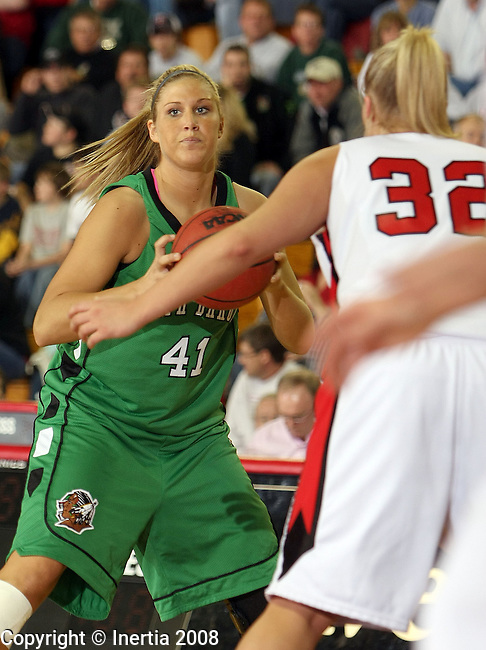 VERMILLION, SD - FEBRUARY 21: Val Sannes #41 of the University of North Dakota  looks for a teammate while being guarded by Bridget Yoerger #32 of the University of South Dakota in the first half of their NCAA basketball game Thursday night at the DakotaDome in Vermillion. (Photo by Dave Eggen/Inertia)
