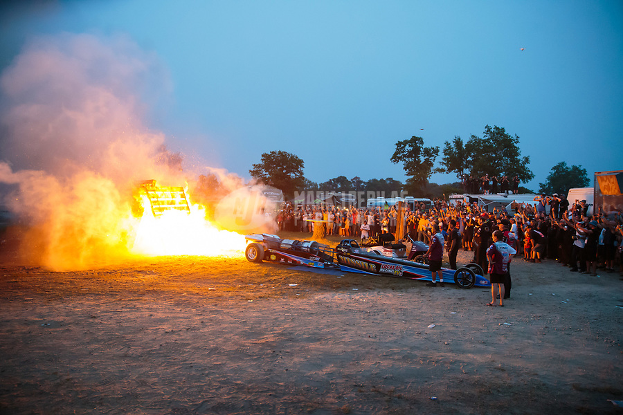 Aug 18, 2018; Brainerd, MN, USA; Fans look on as NHRA jet car driver Tony Franco Jr burns a stack of wood pallets with the afterburner of his jet engine following qualifying for the Lucas Oil Nationals at Brainerd International Raceway. Mandatory Credit: Mark J. Rebilas-USA TODAY Sports
