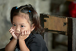 Her chin on her hands, a girl listens to her teacher in a preschool sponsored by the Kapatiran-Kaunlaran Foundation (KKFI) in Pulilan, a village in Bulacan, Philippines.<br /> <br /> KKFI is supported by United Methodist Women.