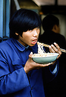 Chinese man wearing Chairman Mao jacket eating noodles with traditional chopsticks in China in the 1980s