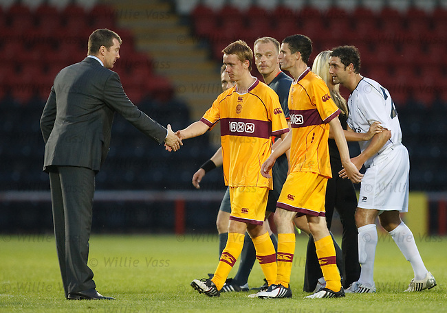 Motherwell's players troop off dejected after defeat and are given a handshake by manager Jim Gannon