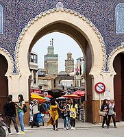 Fes, Morocco.  Young Women in Modern Moroccan Dress Leaving Fes El-Bali (Old City) through the Bab Boujeloud.  The minaret of the Bou Inania medersa is in the background.