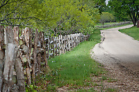 A rail fence  lines the roadsides in the Texas Hill Country near Fredericksburg Texas.