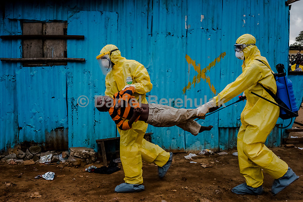 MONROVIA, LIBERIA - SEPTEMBER 05, 2014: James Dorbor, 8, suspected to have Ebola, is rushed in by medical staff wearing protective clothing into the JFK Ebola treatment centre on September 05, 2014 in Monrovia, Liberia.<br /> James Dorbor,8, had been sick and showing symptoms for 3-4 days. Edward Dorbor, his father first took James to the S.O.S clinic, nearby for treatment, but being an ordinary hospital, medical staff were too afraid to treat the boy, as James was suffering with symptoms consistent with Ebola: extreme weakness, loss of appetite, toileting and vomitting. They referred him to the JFK Ebola treatment facility. That day the scene outside of the JFK Ebola treatment Unit was chaotic. One boy lay dead in the back of an ambulance, as three of his family members sat in the back with him. Two family members lay in the back of taxis unable to move and various others in the back of cars. Others people lay strewn over the dirt, underneath a shelter, too weak to stand, lay on benches. James lay outside of the JFK centre for hours. Edward fought hard to get his son to drink fluids but to no avail. James convulsed as he lay on the dirt, outside of the Ebola treatment centre and at one point lay motionless. Onlookers gasped and Edward reacted believing that his son had passed, but the boy still hung on for a few more hours. The gates opened at 4pm and other sick people rushed in to the clinic leaving James on the ground as he was unable to move. His father was too afraid to carry him as he only had a pair of gloves on and onlookers were already worried that he had had too much contact with his son. Edward ran to he heavy gate and beat on the door to get attention and informed them frantically of James condition. After some time medical staff donned protec